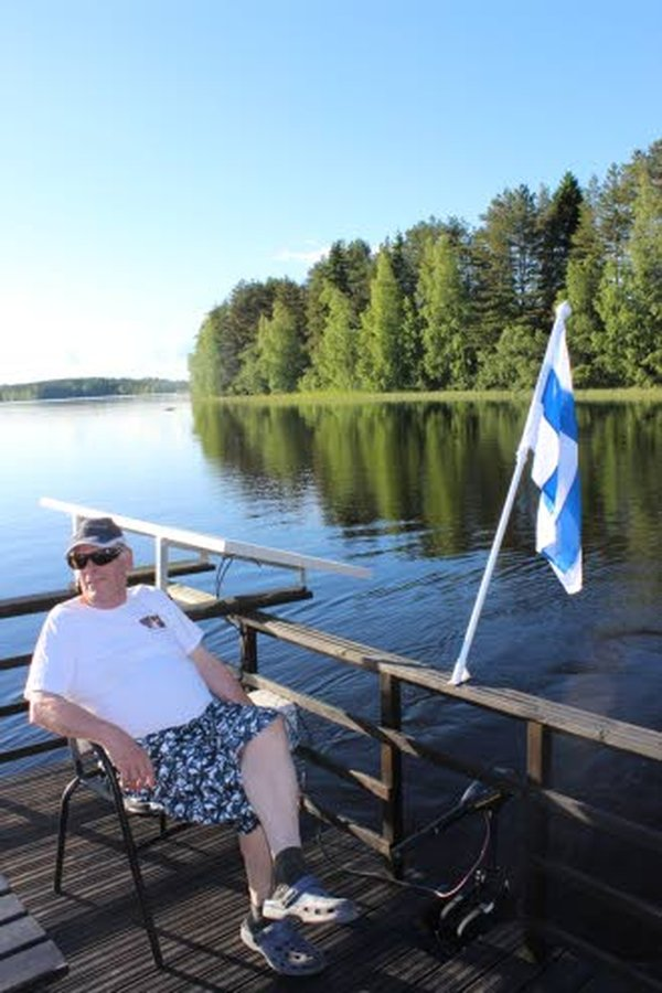 Jussi Pienimäen suunnitteleman ja rakentaman järviristeilijän moottorin akut latautuvat aurinkoenergialla. Aurinkokeräin on kuvassa olevan Jussin takana.