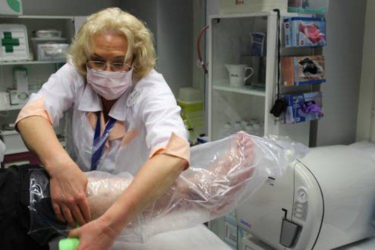 """Pussitushoidossa jalkaan vedetään muovinen, sukan mallinen pussi, joka kiinnitetään ilmatiiviiksi teippisidoksin jalkaan. """"Sukkaan"""" menee muovinen letku, jonka toinen pää on otsonigeneraattorissa, jolla valmistetaan happi-otsoniseos. Tätä johdetaan muoviseen hoitosukkaan viidentoista minuutin ajan."""