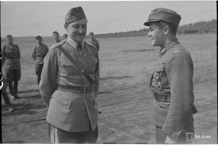 Suomen marsalkka Mannerheim tutustumiskäynnillä Äänislinnassa 21.6.1942. Ylipäällikkö keskustelee kaksi kuukautta aikaisemmin Mannerheim-ristin ritariksi nimitetyn luutnantti Paavo Kahlan kanssa. Tiedustelulennolla Kittilässä 23.10.1944 kadonnut Kahla oli viimeinen kaatunut ritari. Kuva: SA-kuva.