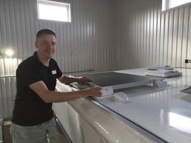 Juha Räihä asentamassa aurinkopaneelia asuntovaunun katolle.